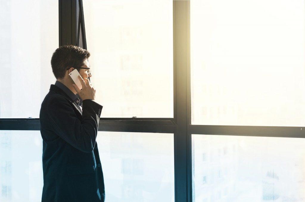 Mann am Fenster mit Telefon